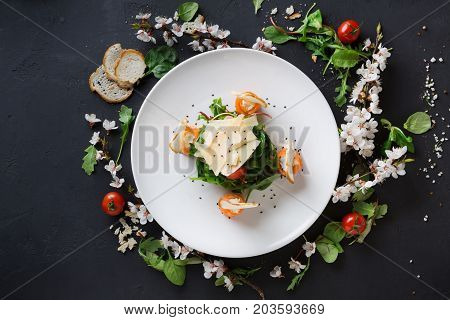 Restaurant dish on white plate on black background decorated with flowers, greens and tomatoes . Salad with spinach, arugula, cheese, salmon and baguette, top view