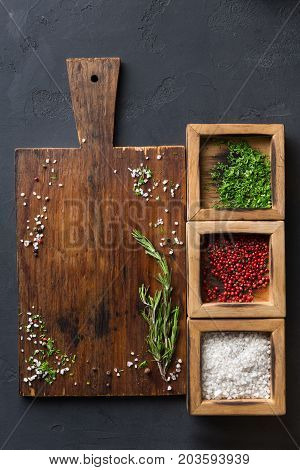 Wooden desk with spices assortment, salt, peppers and parsley in wooden boxes on dark background, top view, copy space.
