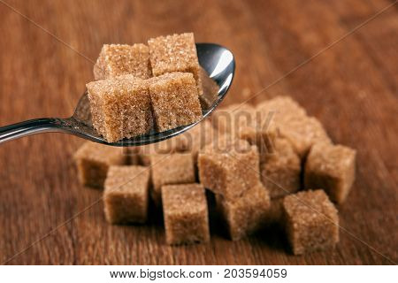 tablespoon with cubes of brown sugar close up