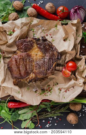 Rib eye steak on cooking paper, parchment with vegetables and spices border on dark background, top view, close up