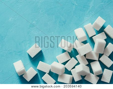 sugar cubes on blue concrete background. Top view of white sugar on turquoise table. Sugar with copy space. Top view or flat lay