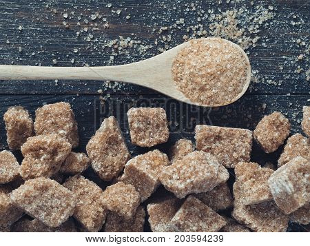 natural raw brown cane sugar cubes and granulated brown sugar in spoon close up as background. Top view of brown sugar