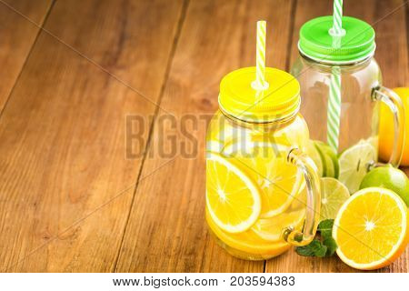 Two Jars Of Detox Water With Slices Of Orange And Lime.