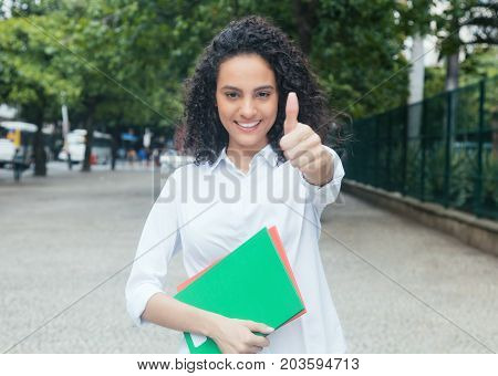 Latin female student with curly hair and white shirt showing thumb outdoor in the city