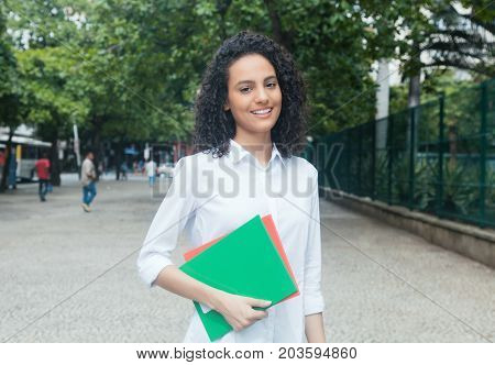 Laughing latin female student with curly hair and white shirt outdoor in the city