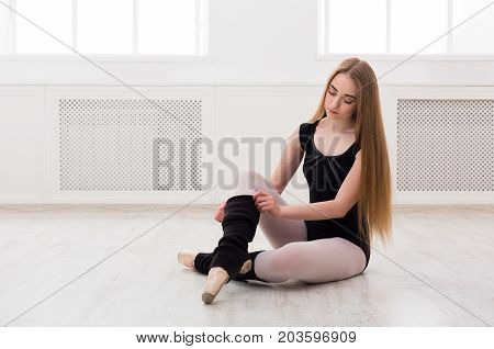 Beautiful graceful ballerina in black stretching in class room background. Ballet class training, copy space