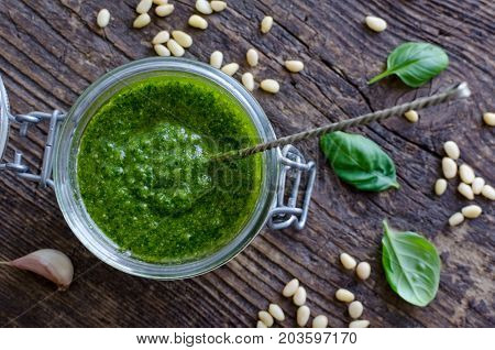 Pesto genovese - traditional Italian green basil sauce with pine nuts basil and garlic on rustic wooden background. Top view.