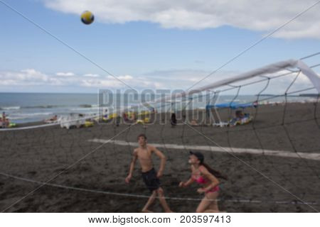 Beach background from photo blurred lens. summer vacation sport and people concept - young Friends with ball playing volleyball on beach