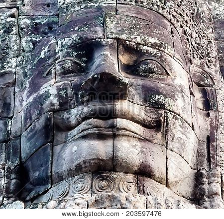 Ancient stone faces of king Bayon Temple Angkor Thom Cambodia. Ancient monument Khmer architecture Kampuchea.