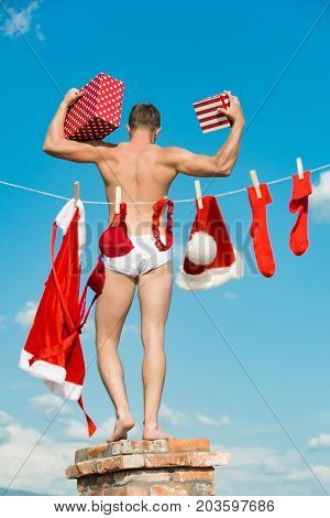 New Year Guy With Muscular Body On Blue Sky.
