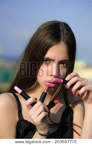 Woman Posing With Pink Lips And Lipsticks On Blue Sky