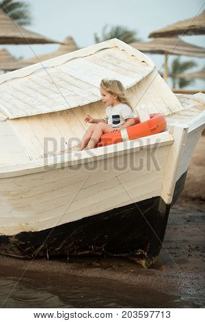 Small Kid Sit On Wooden Boat At Beach.