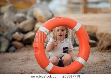 Kid looking through orange life ring at beach. Emergency and safety on water on summer vacations. Boy child playing with life saver. Baby care and childhood concept. Happiness and expressive emotions.