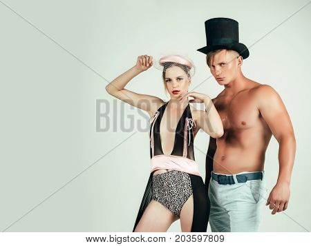 Couple in love posing on grey background. Woman or girl wearing sexy lingerie and veil hat. Man or macho with muscular torso in black top hat. Fitness and beauty. Fashion and style concept copy space
