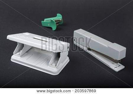 Metal stapler and puncher on the black background
