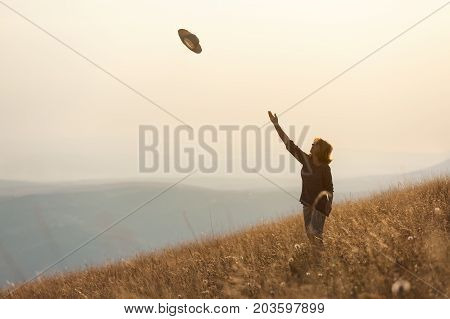 Happy woman enjoying the nature feel free and throwing her hat in the air toward the setting sun. Lifestyle and celebration concept.