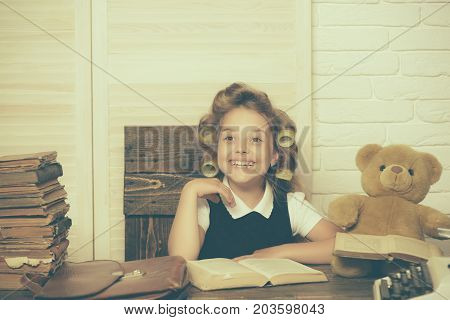 Kid reading book. Little baby secretary in cabinet with bear. Child play in school. Education and childhood. Small girl with curler in hair.
