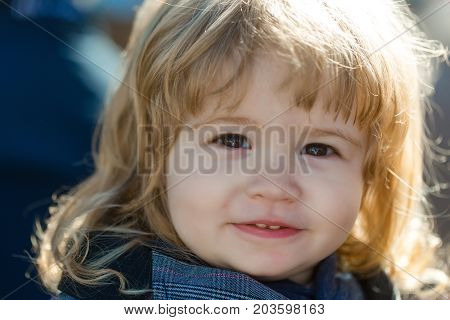 Toddler boy with cute face. Child with brown eyes. Kid with long blond hair. Baby on sunny day outdoors. Happy childhood concept.