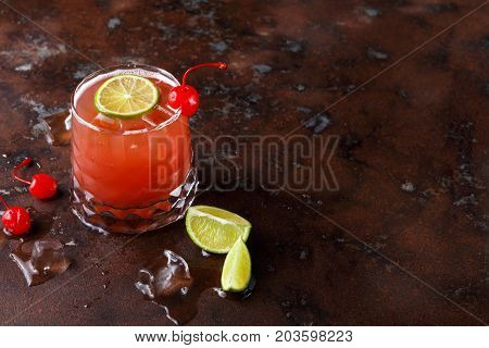 Red cocktail on brown background. Refreshing alcohol drink with tequila, citrus juice, lime and maraschino cherry on dark marbled table with meltig ice, copy space