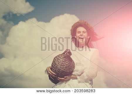 Happy woman in white dress and wreath on brunette hair. Summer vacation holidays and celebration. Harvesting and winemaking. Winery tour concept. Girl smiling with wicker wine bottle on cloudy sky.