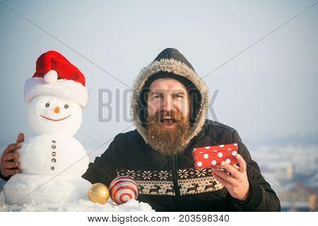 Happy Man And Snowman In Santa Hat On Grey Sky