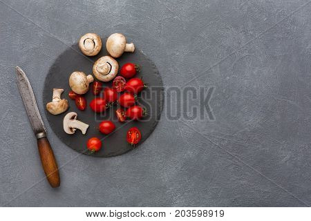 Cut tomatoes and mushrooms on rustic slate stone plate. Cooking healthy food on gray background, copy space, top view.