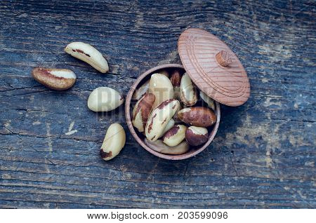 Tasty Brazil nuts from Bertholletia excelsa tree in wooden bowl on the old background. Healthy edible seeds food ingredient on the table. Top view.