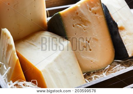 Cheese assortment closeup. Edammer, gruyere, pecorino at grocery shop in wooden box, cheese grocery background