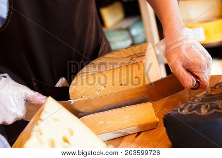 Cutting aged cheese, parmesan cheese in grocery shop, closeup