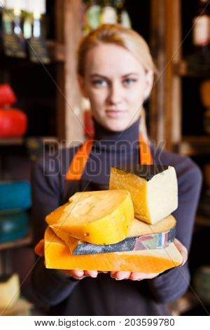 Aged italian cheese assortment. Female shop assistant suggesting parmesan and pecorino cheese, grocery shop background