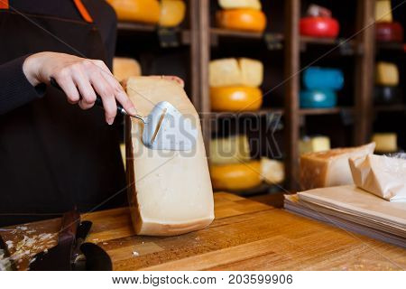Parmesan cheese closeup. Half wheel of cheese on wooden table. Shop assistant slicing cheese with special knife, background, copy space