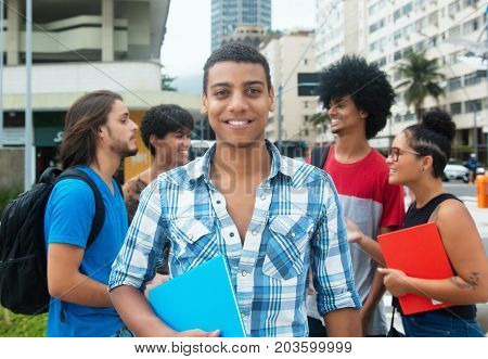 Happy hipster male student with group of multi ethnic young adults outdoor in city