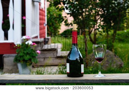 Bottle of red wine with the cork in the neck and a goblet of wine standing on the Board on the background of a country house.