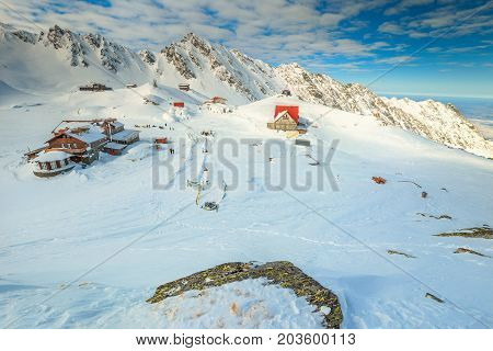 Spectacular winter landscape in Fagaras mountains with famous frozen Balea lake and wooden houses Carpathians Transylvania Romania Romania
