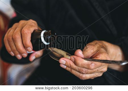 An elderly woman pours medicine in a spoon, caring for the health of old people concept