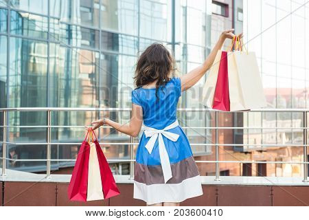Shopper. Shopaholic shopping woman holding many shopping bags excited
