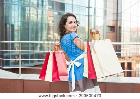 happiness, consumerism, sale and people concept - smiling young woman with shopping bags over mall background.