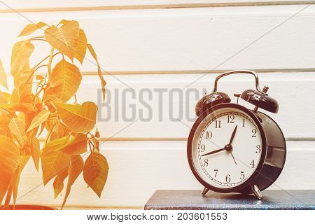 Round table clock - alarm clock on a white wooden wall background, sunlight effect, copy space