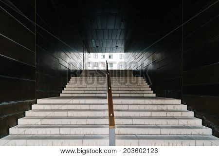 Frontal view of modern staircase in passageway.