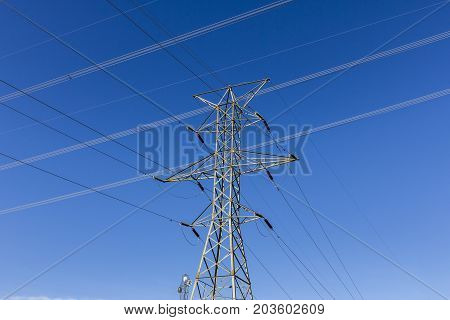 High-voltage power lines and pylon against blue sky