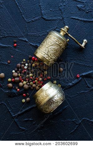 Vintage pepper mill and black red and white peppercorns on dark stone table. Spices concept. Food flat lay. Top view.