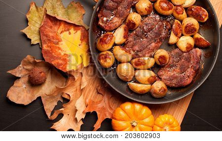 Roast beef steak with roasted potatos in copper pan on wooden table top view. Autumn mood
