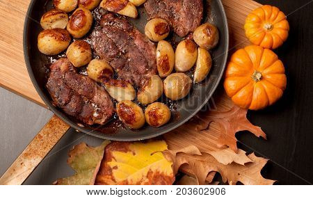 Roast Beef Steak With Roasted Potatos In Copper Pan On Wooden Table, Top View.