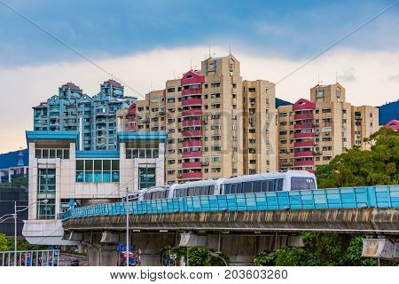 TAIPEI TAIWAN - JULY 01: This is Dahu park MRT station with a train arriving in the station and city buildings in the background on July 01 2017 in Taipei