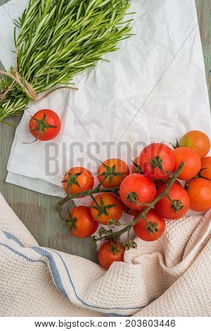 Organic cherry tomatoes with rosemary on wrinkled paper. Top view