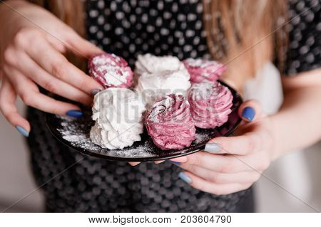 Young woman eats colorful sweet zephyrs on black plate. Delicious confectionery and cookies temptation, homemade dessert for breakfast, close up