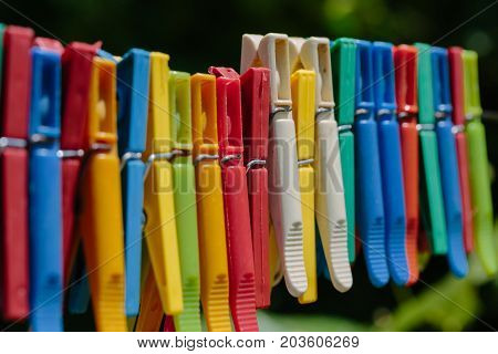 Colorful group of clothespins on a rope. Photo in the daytime.