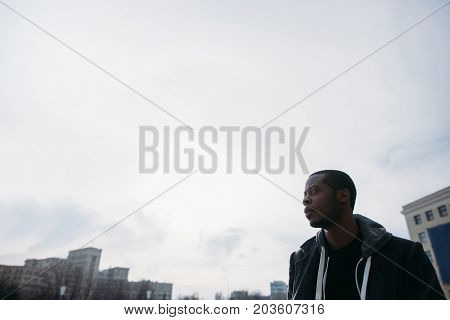 Thoughtful black male outdoors. Cloudy sky. White background with free space, urban style, rainy weather, fashion man model
