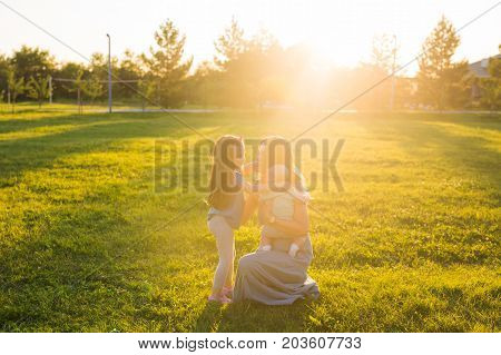 Beautiful woman with daughter and baby son on green grass field. Mother with two little children hugging outdoors. Happy family concept.