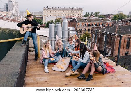 Students birthday party on roof. Leisure time. Music and pizza for young people